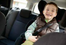 Glad pojke i bilbarnstol
